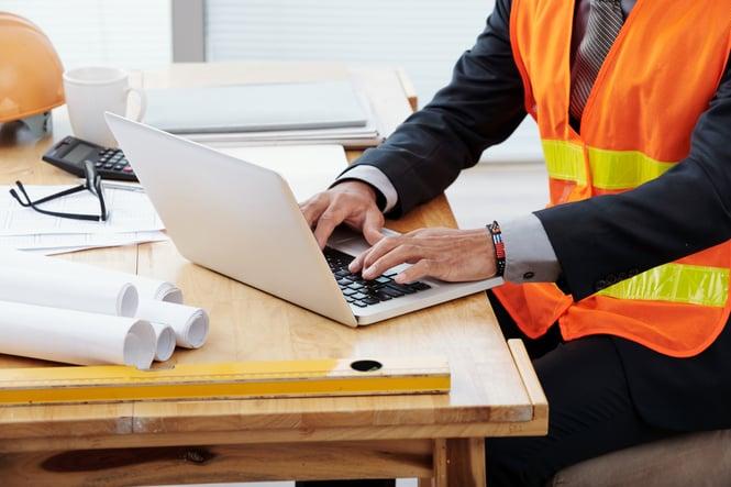 unrecognizable-man-neon-safety-vest-business-suit-sitting-desk-using-laptop